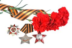 Red carnations tied with Saint George ribbon, orders of Great patriotic war Stock Photos