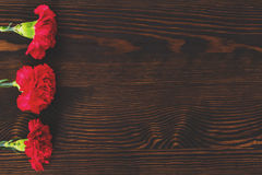 Red carnations on wood table Royalty Free Stock Images