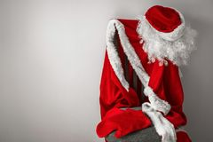 A fairy tale made by own hands. The red carnival costume of Santa Claus hangs on a chair. Preparing for a holiday, buying gifts, waiting for miracles and Royalty Free Stock Photos