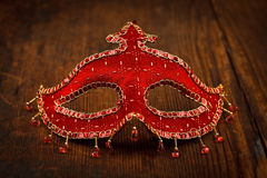 Red carnival mask on wooden table Royalty Free Stock Photography