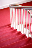 Red carpet. Stairs covered with a thick red carpet  and a wooden handrail leading to a landing Stock Images