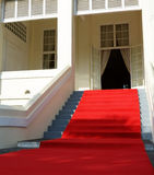 Red carpet event. Regal red carpet rolled out in front of mansion for event royalty free stock photography