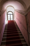 Red carpet leading up stone staircase with vaulted ceiling Royalty Free Stock Photos
