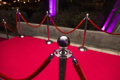 Red carpet. Long red carpet between rope barriers on VIP entrance Royalty Free Stock Photography
