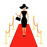 Red carpet and rope barrier golden stanchions turnstile Isolated Woman in black hat, bag, sunglasses waving.  Stock Images
