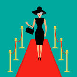 Red carpet and rope barrier golden stanchions turnstile  Woman in black hat, bag, sunglasses waving. Rich beautiful celebr Royalty Free Stock Photography