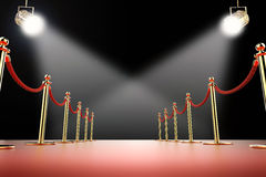 Red carpet and rope barrier with shining spotlights Stock Photos