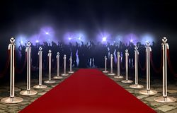 Red carpet between rope barriers and crowd royalty free stock photo