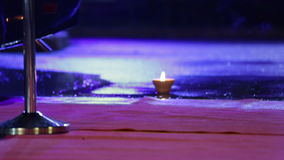 Red carpet soaked with water with a burning candle stock footage