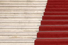 Red carpet on stairs. Close up of red carpet on white stairs viewed at angle Royalty Free Stock Images