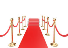 Red carpet and stairs between two gold stanchions with rope. Royalty Free Stock Images