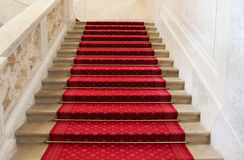 Red carpet on a stairway. Concept or background for richness, fa Stock Photos