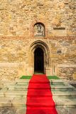 Red carpet to the church. Red carpet in front of an orthodox church in Borzesti, Romania, near Onesti. The church was made by king Stefan cel Mare in 1493 and Royalty Free Stock Photos