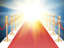 Red carpet between two gold stanchions with rope Royalty Free Stock Photo