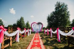 Red carpet wedding arch and chairs for ceremony decorated. With white and pink fabric and flowers Royalty Free Stock Photography