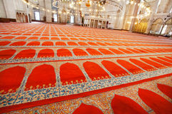 Red carpets with traditional patterns on floor of 16th century Suleymaniye Mosque with bright lights Stock Photo