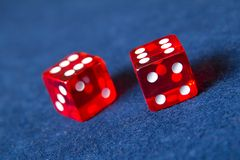 Red casino dice. Pair of red casino dice on blue table stock photos