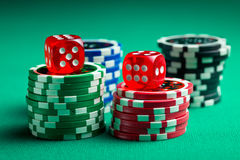 The red casino dice and casino chips. On green table royalty free stock photography