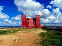 Red castle. In countryside malta surrounded by green meadows Stock Photography