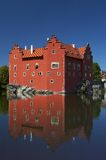 Red castle on lake. Old historic, medieval castle with bright red bricks on the shore of a quiet lake Royalty Free Stock Photo