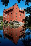 Red castle on lake. Old red brick castle build on the shore of a lake Royalty Free Stock Photography