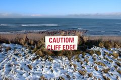 Red caution sign on hazardous cliff edge Royalty Free Stock Photos