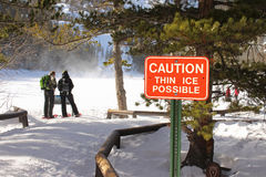 A red caution sign warns hikers of possible thin ice across a frozen lake. Stock Image