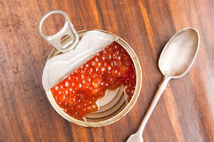 Red caviar in bank with spoon on wood Royalty Free Stock Image