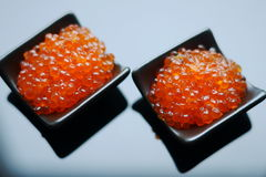 Red caviar. In black  bowl on black glass background Royalty Free Stock Image