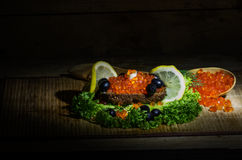 Red caviar and black bread. Still life with red caviar, black bread and fresh herbs Stock Photo