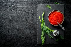 Red caviar in a bowl on a black stone Board with salt and dill. On black rustic background royalty free stock image