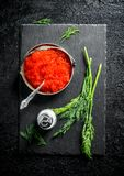 Red caviar in a bowl on a black stone Board with salt and dill. On black rustic background royalty free stock photos