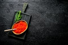 Red caviar in a bowl on a cutting Board with dill. On black rustic background royalty free stock photo