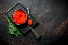 Red caviar in a bowl and a spoon on a cutting Board with dill. On dark rustic background royalty free stock photo