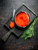 Red caviar in a bowl and a spoon on a cutting Board with dill. On dark rustic background stock image