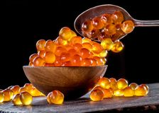 Red caviar in the bowl on wooden background royalty free stock photos