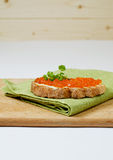 Red caviar with bread. And butter on cutting board Stock Photography