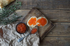 red caviar with bread, butter and herbs on vintage board, Sandwich with red caviar Royalty Free Stock Photo