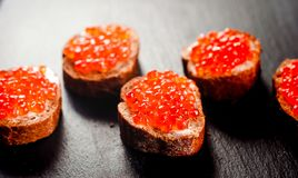 Red caviar on bread on slate background. stock photo