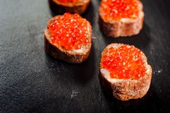 Red caviar on bread on slate background stock photo