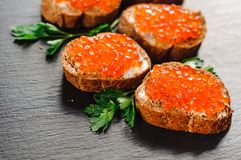 Red caviar on bread on slate background. royalty free stock photo