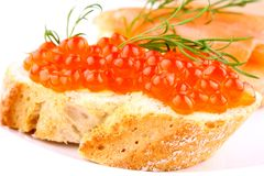 Red caviar on bread on white plate closeup Stock Photography