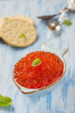 Red caviar in fish-shape bowl with crackers Royalty Free Stock Photo