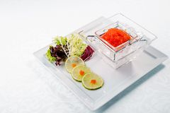 Red caviar in ice close up with lime. Sea food. wooden. Healthy eating Royalty Free Stock Photo