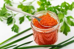 Red caviar jar with spoon and herbs. On the table stock photo