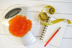 Red caviar on the kitchen scale next to the notepad and tape measure. Counting the amount of protein, calories and fat in food stock photos