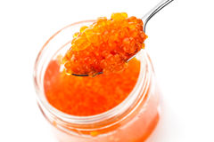 Red caviar in metal spoon and full glass jar Royalty Free Stock Photos