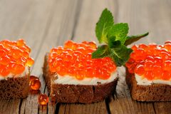 Red caviar on rye bread and butter with fresh mint Stock Photo