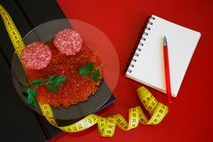 Red caviar, salami and parsley leaves next to the notepad and tape measure. Counting and recording the amount of protein, calories royalty free stock image
