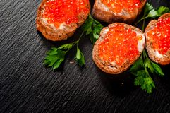 Red caviar on slate background. stock image